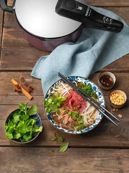 Vietnamesische Pho Bo mit Rindfleisch, Reisnudeln, Kräutern und Röstzwiebeln